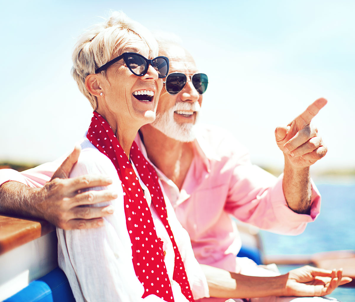 Two adult seniors on a boat in sunglasses with the sun shinning